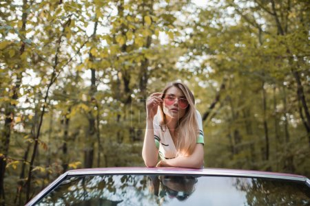 Photo for Stylish woman touching sunglasses and looking at camera while leaning on windshield of cabriolet - Royalty Free Image