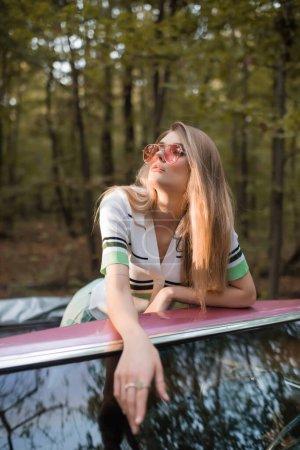 mujer elegante mirando hacia otro lado, mientras que de pie en cabriolet en primer plano borrosa