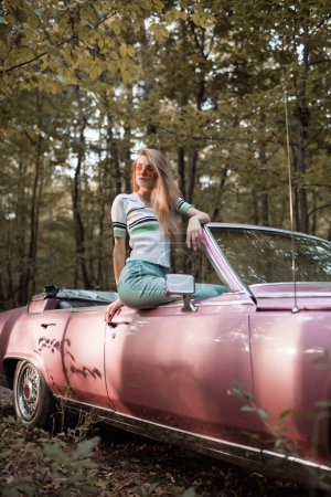 femme élégante dans des lunettes de soleil regardant loin tout en étant assis sur la porte de la voiture convertible