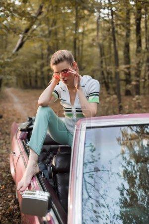 élégant pieds nus femme touchant des lunettes tout en étant assis dans le cabriolet sur le premier plan flou