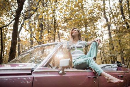 Photo pour Souriant pieds nus femme en lunettes de soleil posant en voiture convertible en forêt - image libre de droit