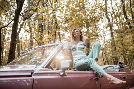 Photo for Happy barefoot woman touching hair and looking away while posing in cabriolet in sunshine on blurred foreground - Royalty Free Image
