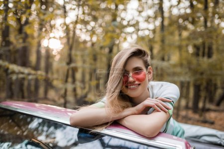 joyful woman in sunglasses looking at camera while leaning on windshield of cabriolet with crossed arms