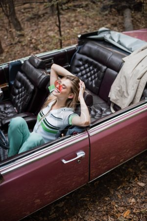 high angle view of joyful woman relaxing while sitting in cabriolet with closed eyes and hands behind head