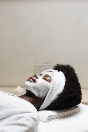 Curly african american woman lying with face mask with blurred candle on background