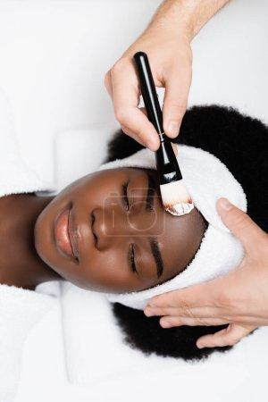 Photo pour Vue du dessus de la femme afro-américaine souriante en bandeau blanc couché près de l'homme avec une brosse cosmétique dans un salon de spa - image libre de droit
