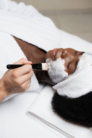 Positive african american woman in headband lying near spa therapist applying face mask on cheek in spa salon