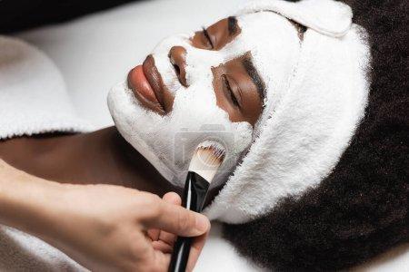 Vista de cerca de la mujer afroamericana positiva con diadema que miente cerca del terapeuta del balneario que aplica la máscara facial en la mejilla en el salón del balneario