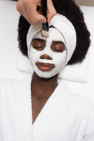top view of positive african american woman wearing bathrobe, lying near spa therapist applying face mask on forehead in spa salon