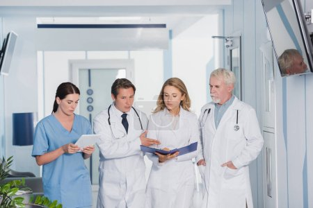Selective focus of doctor pointing near colleagues with digital tablet and clipboards in clinic