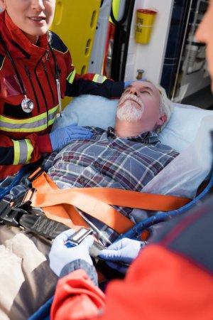 Selektiver Fokus des Sanitäters, der in der Nähe des Patienten steht, während der Kollege das Band der Trage im Freien verriegelt