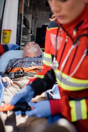 Photo pour Concentration sélective de l'homme âgé couché sur civière près des ambulanciers et de la voiture d'ambulance - image libre de droit