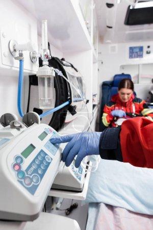 Selektiver Fokus des Sanitäters mit Geräten in der Nähe des Kollegen im Rettungswagen