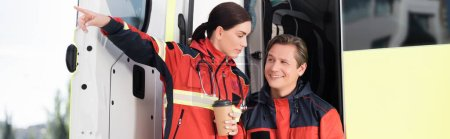 Photo for Horizontal image of paramedic looking away near colleague with paper cup pointing with finger and ambulance car - Royalty Free Image