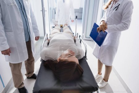 Photo for Selective focus of patient lying on stretcher near doctors in clinic - Royalty Free Image