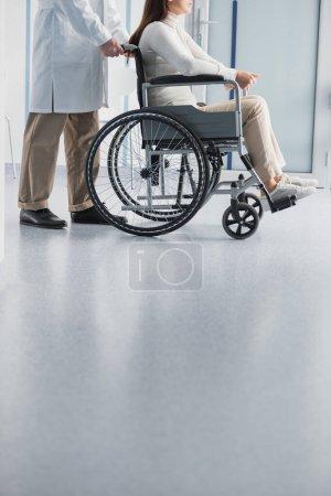 Photo pour Vue recadrée du médecin debout près du patient en fauteuil roulant à la clinique - image libre de droit
