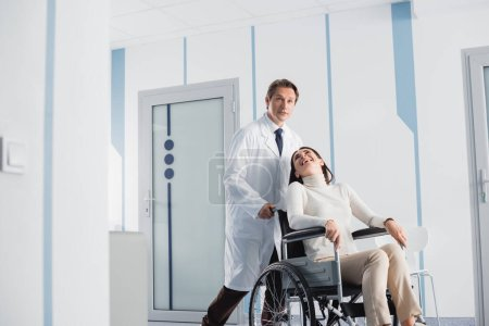 Photo for Selective focus of excited patient in wheelchair looking at doctor in clinic - Royalty Free Image