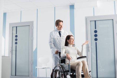 Photo pour Brunette femme en fauteuil roulant pointant avec la main tout en étant assis en fauteuil roulant près du médecin à l'hôpital - image libre de droit