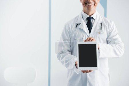 Photo pour Vue recadrée du médecin avec stéthoscope montrant tablette numérique en clinique - image libre de droit
