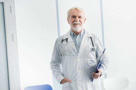 Photo for Grey haired doctor with hand in pocket holding clipboard in hospital - Royalty Free Image