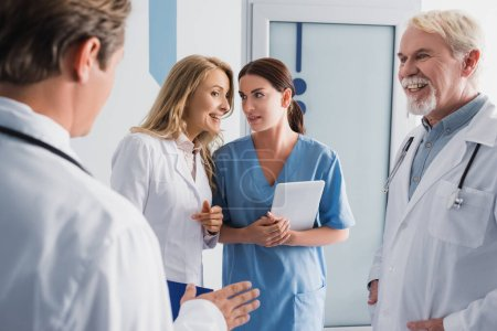 Photo for Selective focus of doctor talking to nurse with digital tablet near colleagues in clinic - Royalty Free Image