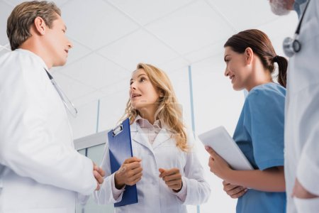 Photo for Selective focus of doctors and nurse with digital tablet talking in clinic - Royalty Free Image