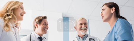 Photo for Panoramic shot of doctors looking at nurse while talking in clinic - Royalty Free Image