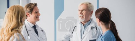 Photo for Panoramic crop of doctors and nurse with digital tablet looking at colleague during conversation in clinic - Royalty Free Image