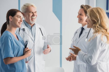 Photo for Selective focus of doctors in white coats and nurse with digital tablet talking in hospital - Royalty Free Image