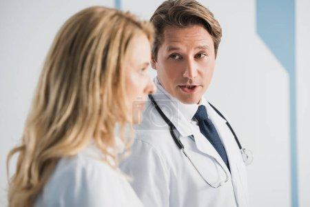 Photo pour Concentration sélective du médecin regardant un collègue tout en parlant à la clinique - image libre de droit