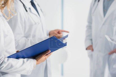 Photo pour Vue recadrée du médecin tenant le presse-papiers près de ses collègues en clinique - image libre de droit