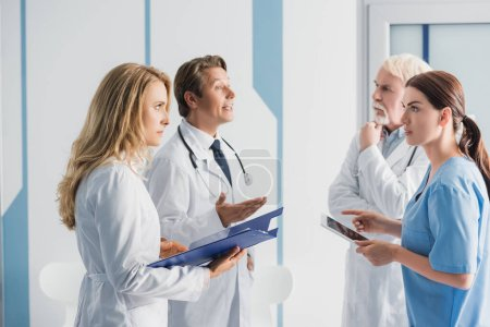 Photo for Selective focus of doctors with clipboard and nurse with digital tablet talking in clinic - Royalty Free Image