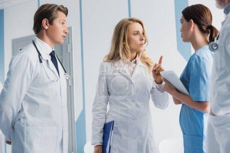 Selektiver Fokus des Arztes mit Klemmbrett, das mit dem Finger auf Kollegen und Krankenschwester mit digitalem Tablet zeigt