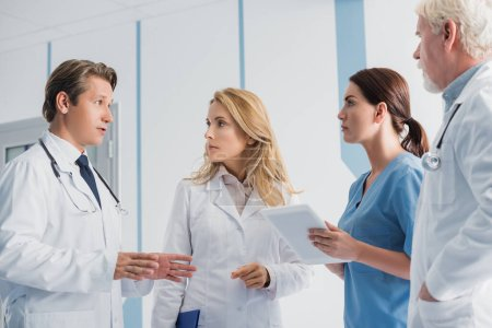 Selective focus of doctor pointing with hands near colleagues and nurse with digital tablet