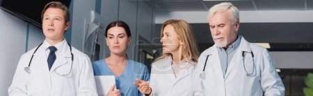 Horizontal crop of doctor pointing with finger near colleagues and nurse with digital tablet
