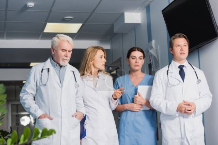 Selective focus of doctor with clipboard pointing with finger near nurse with digital tablet and colleagues in clinic