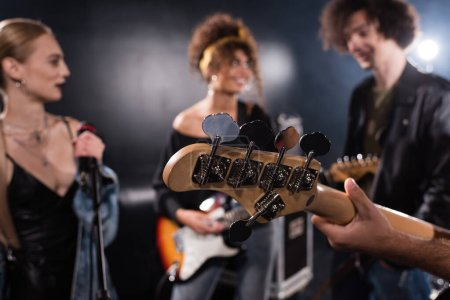 Photo for KYIV, UKRAINE - AUGUST 25, 2020: Musician holding electric guitar with blurred rock band members on background - Royalty Free Image