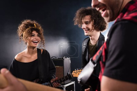 Smiling musician standing near curly woman with bass guitar with blurred guitarist on foreground