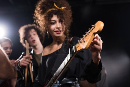 Curly woman touching and looking at electric guitar, while standing near musician pointing with finger on blurred background