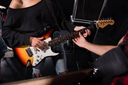 KIEW, UKRAINE - 25. AUGUST 2020: Ausgeschnittene Ansicht eines Mannes, der Gitarrensaiten berührt, während eine Frau während einer Rockband-Probe spielt