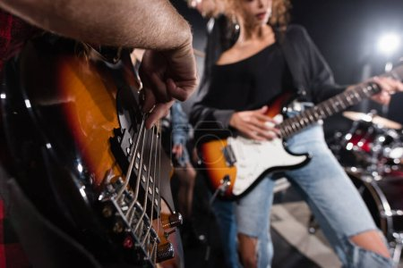 KYIV, UKRAINE - AUGUST 25, 2020: Cropped view of man playing bass guitar near female musician with backlit on blurred background
