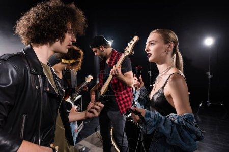 Foto de KYIV, UCRANIA - 25 de agosto de 2020: Músico de banda de rock y mujer rubia con micrófono hablando cerca de guitarristas con retroiluminación en el fondo - Imagen libre de derechos