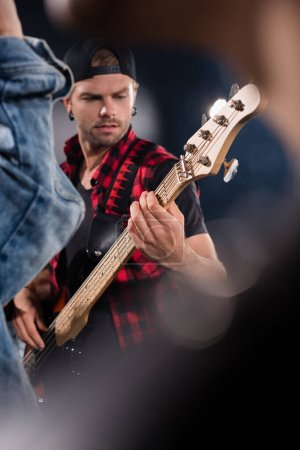 KYIV, UKRAINE - AUGUST 25, 2020: Rock band musician playing electric guitar on blurred foreground