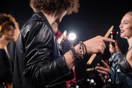 Curly man with drumstick pointing with finger during rehearsal with blurred rock band musicians on background