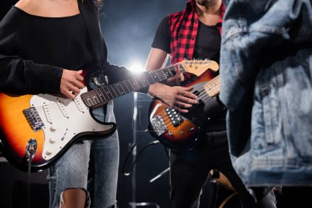 Photo for KYIV, UKRAINE - AUGUST 25, 2020: Cropped view of rock band musicians playing electric guitars with blurred jeans jacket on foreground - Royalty Free Image