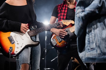 KYIV, UKRAINE - AUGUST 25, 2020: Cropped view of rock band musicians playing electric guitars with blurred jeans jacket on foreground