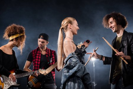 Photo for KYIV, UKRAINE - AUGUST 25, 2020: blonde vocalist talking with drummer standing near musicians playing electric guitars with backlit on black background - Royalty Free Image