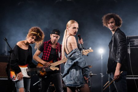 Photo for KYIV, UKRAINE - AUGUST 25, 2020: Rock band musicians with electric guitars, drumsticks and microphone looking at camera with backlit on black - Royalty Free Image