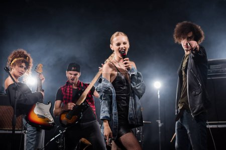 KYIV, UKRAINE - AUGUST 25, 2020: Blonde woman singing in microphone standing near musician pointing with drumstick and guitarists with backlit on black