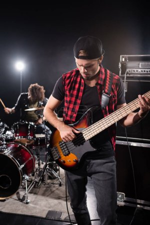 Foto de KYIV, UCRANIA - 25 de agosto de 2020: Músico de la banda de rock tocando el bajo, de pie cerca del amplificador combinado con batería borrosa y kit de batería en el fondo - Imagen libre de derechos